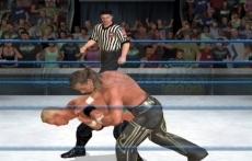 Review WWE SmackDown vs. Raw 2010: Hier zie je een gevecht en daar achter de scheidsrechter! Het grappige is dat je de scheidsrechter ook nock-out kan slaan en trucjes op hem doen!